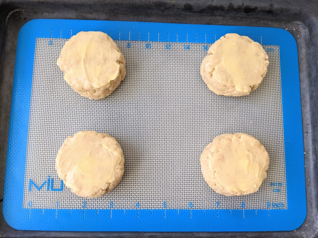 biscuits topped with butter and ready to bake